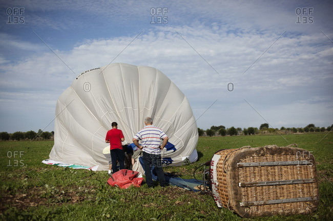 Hot air balloon crew deflating the balloon on the ground