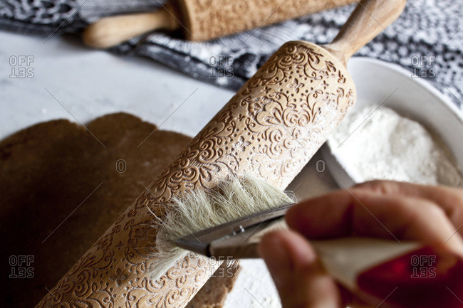 Dusting an embossed rolling pin with flour