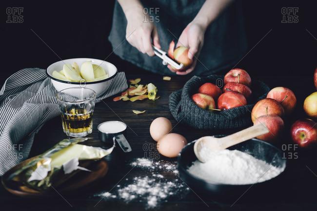 Hand peeling apples with cake ingredients