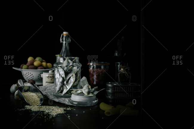 Fish and various ingredients on dark background