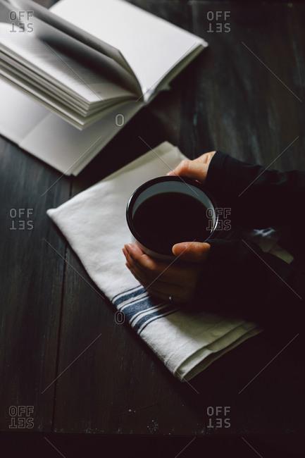 Hand cupping coffee mug by book