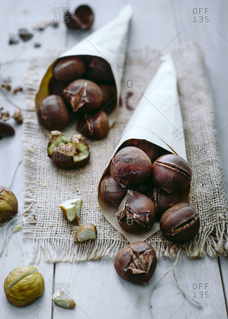Roasted chestnuts spilling from paper cones