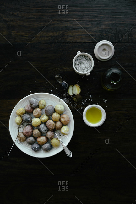 Plate of small baked potatoes and seasonings