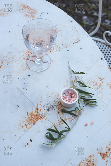 Rock salt, glass, branch on scratched table