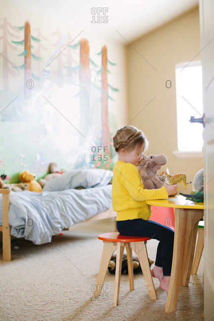 Girl playing with toys in her bedroom