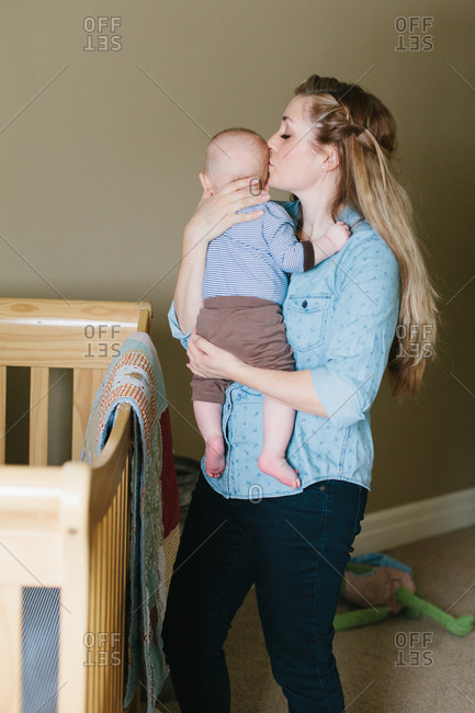 Mother kissing her baby next to a crib