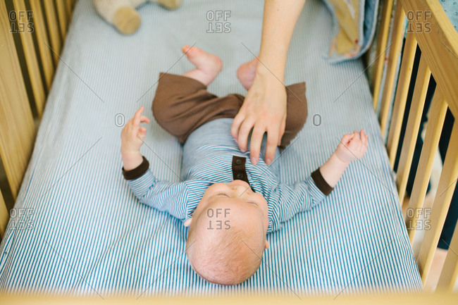 Mother tickling her baby in his crib