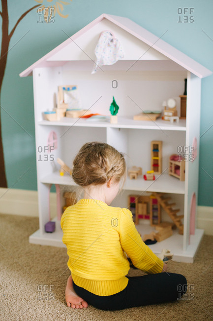 Girl playing with her doll house