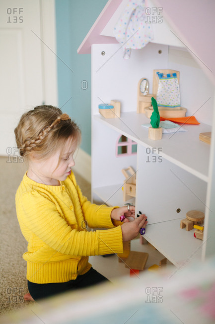 Little girl playing with her doll house