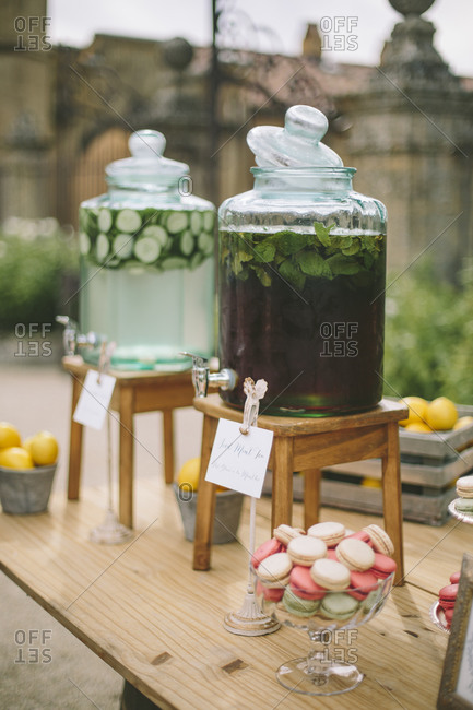 Drinks in dispensers by macaroons at wedding
