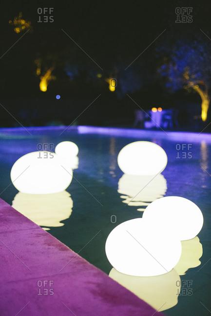 Illuminated globes floating in pool
