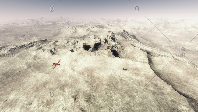 Red single engine airplane flying over barren mountain landscape