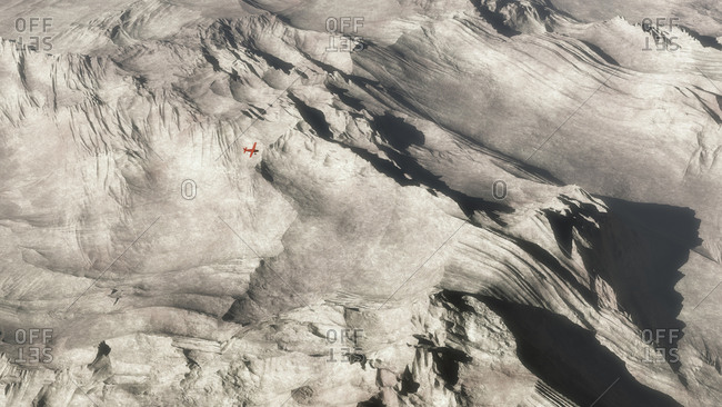 Aerial of small red  airplane over barren mountain landscape