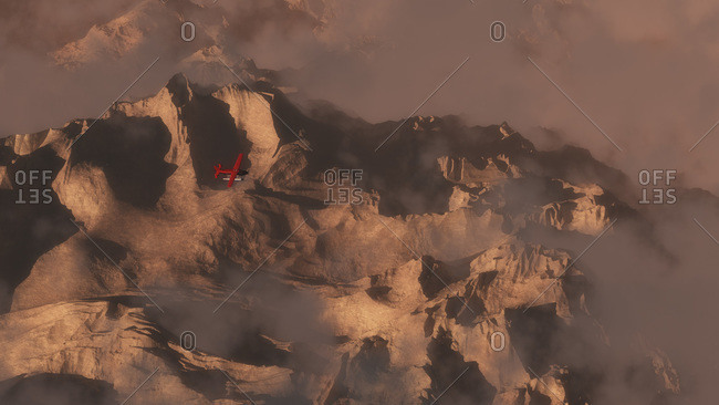 Aerial of mountains in morning mist with single engine airplane flying over