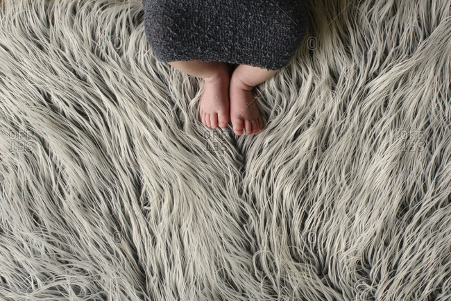 Feet of a baby lying on a furry blanket