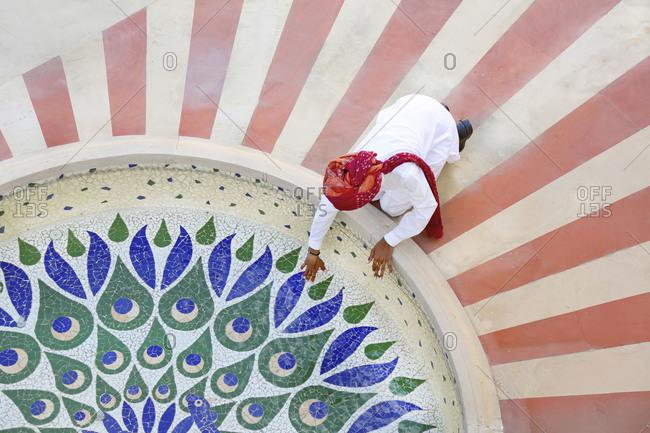 Worker reaching into fountain pool in Jaipur, India