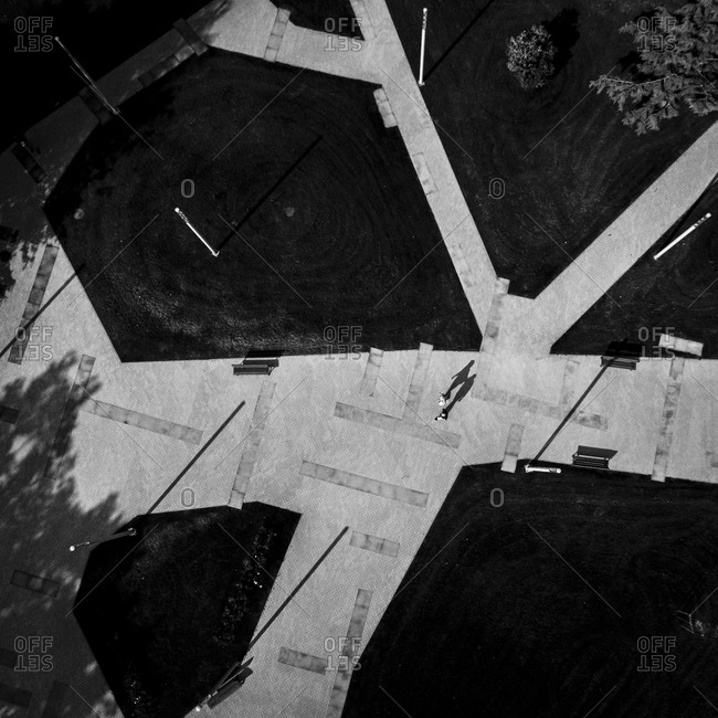 Black and white aerial view of couple walking on a path in Nida, Lithuania