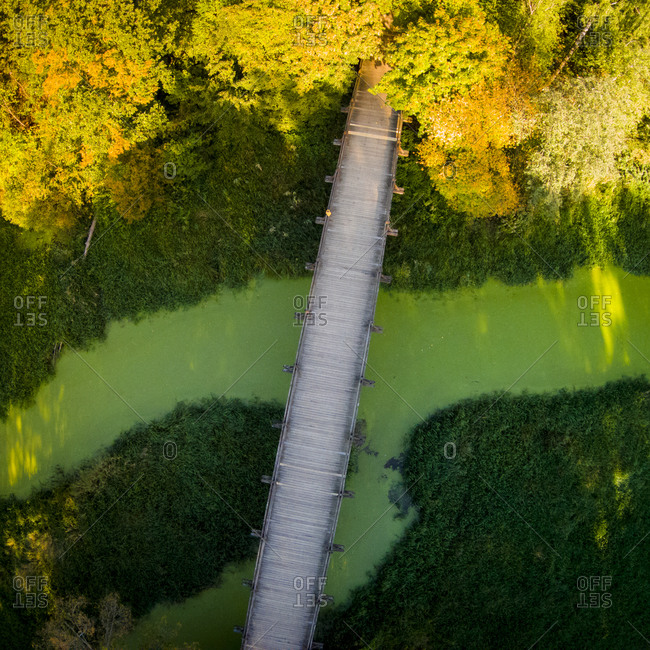 Aerial view of wooden bridge over green river in Lithuania