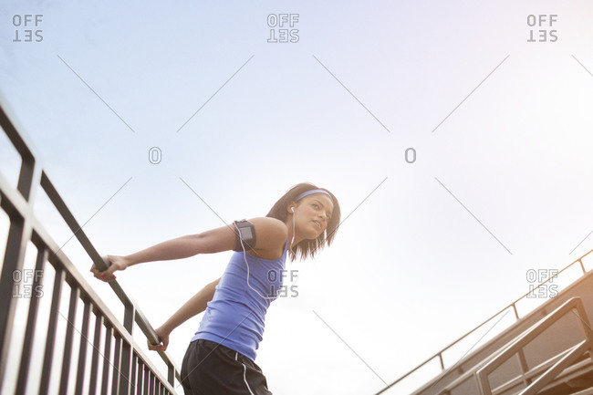 Woman wearing headphones and music player in armband stretches before workout
