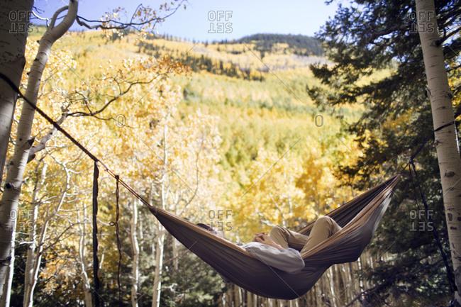 Backpacker lying in hammock strung between two aspen trees