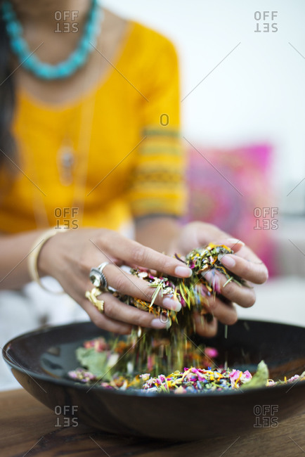 Herbalist mixing flowers and leaves for a blend of herbs