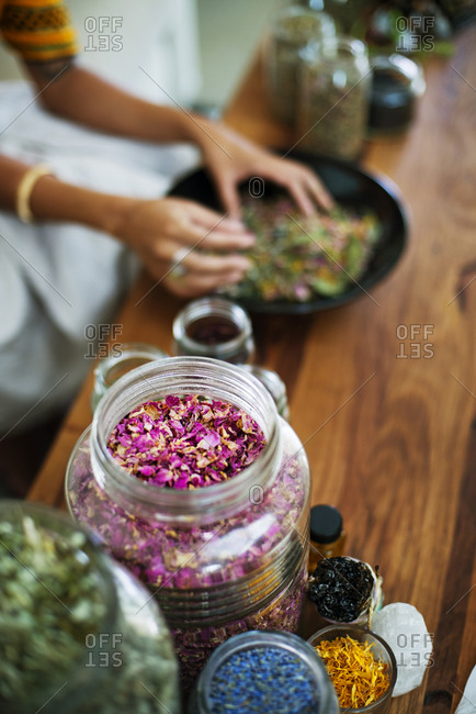Overhead view of an herbalist preparing a blend of herb flowers and leaves