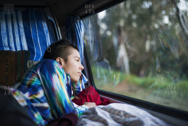 Woman lying in back of camper van and gazing out the window