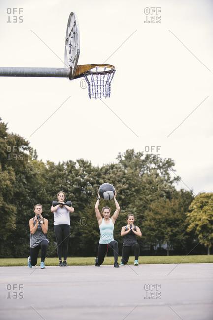 Four women having an outdoor boot camp workout