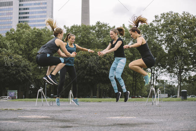 Four women jumping during an outdoor workout