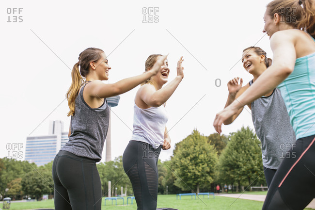 Four happy women high fiving after an outdoor workout