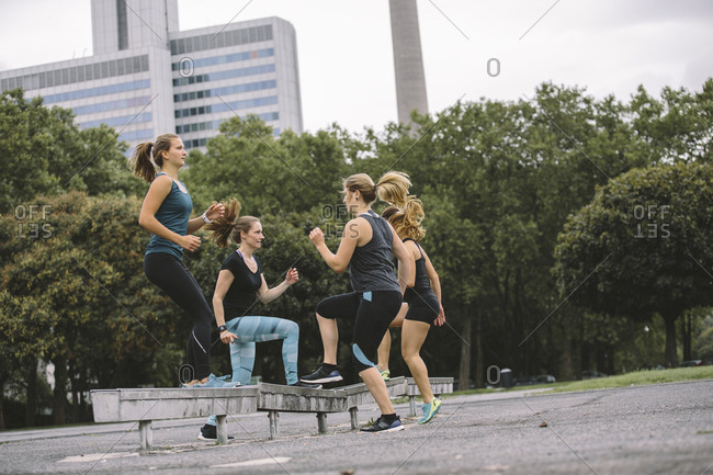 Four women doing step ups during an outdoor workout