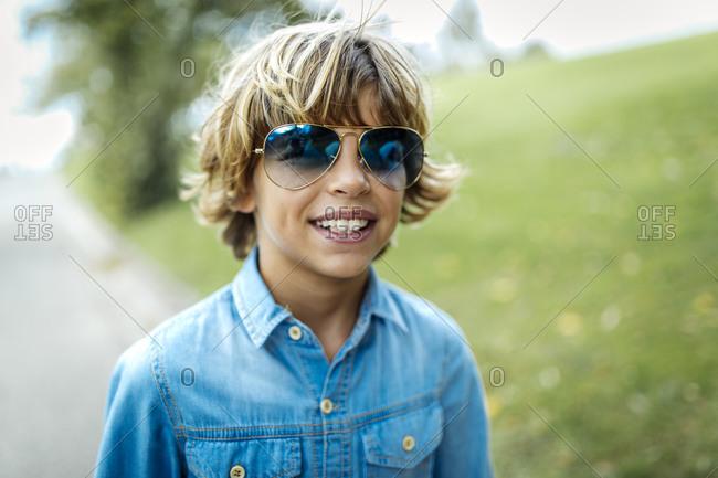 Portrait of blond boy wearing blue sunglasses and denim shirt