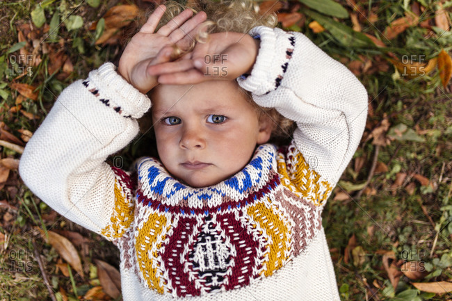 Portrait of pouting blond little boy wearing patterned knit pullover
