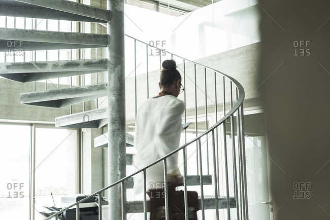 Young woman in office walking up spiral staircase