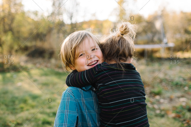 Boy getting a big hug from his sister