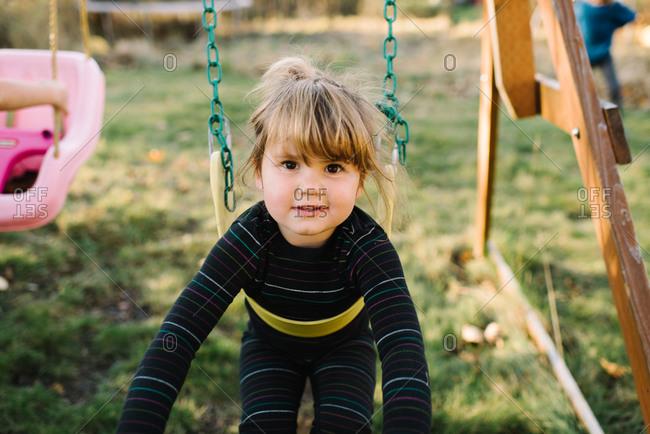 Little girl swinging on a swingset