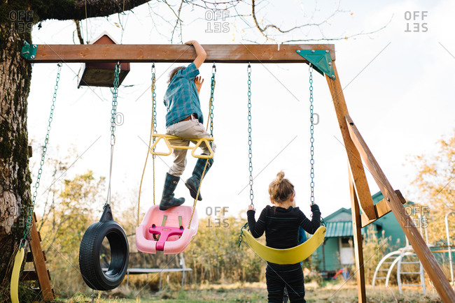 Children playing on backyard swingset