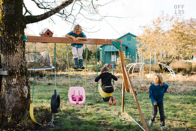 Children playing on swingset in backyard