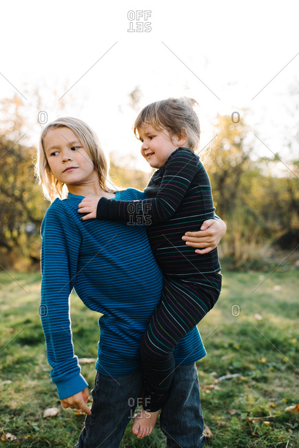 Older brother lifting his little sister