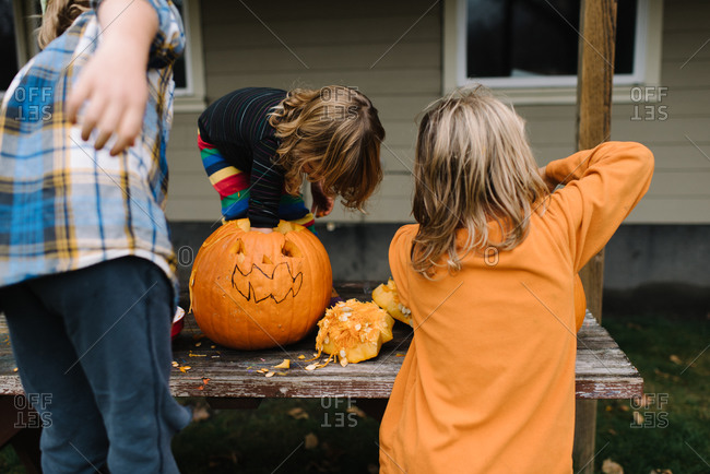 Kids carving pumpkins on a picnic table