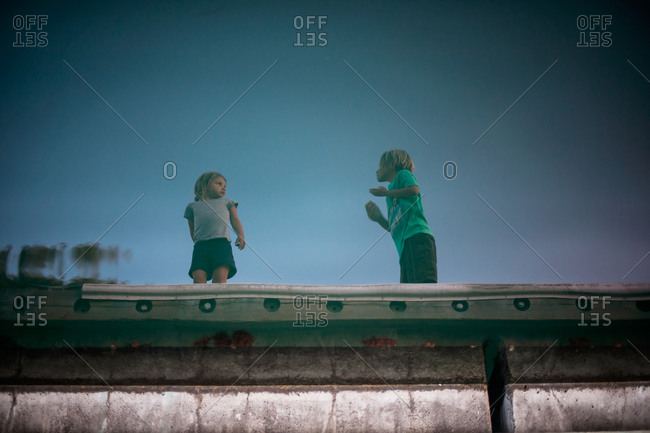 Reflection in water of children standing on a pier
