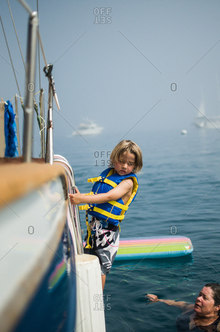 Little boy climbing a ladder on a boat