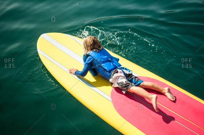 Little boy floating on a surfboard in the ocean