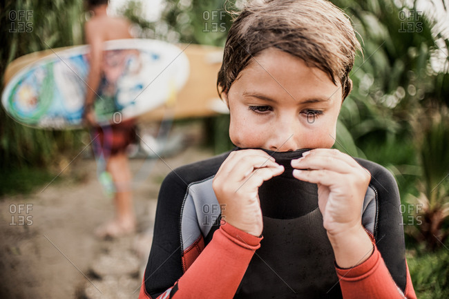 Little boy wiping his mouth on his wetsuit