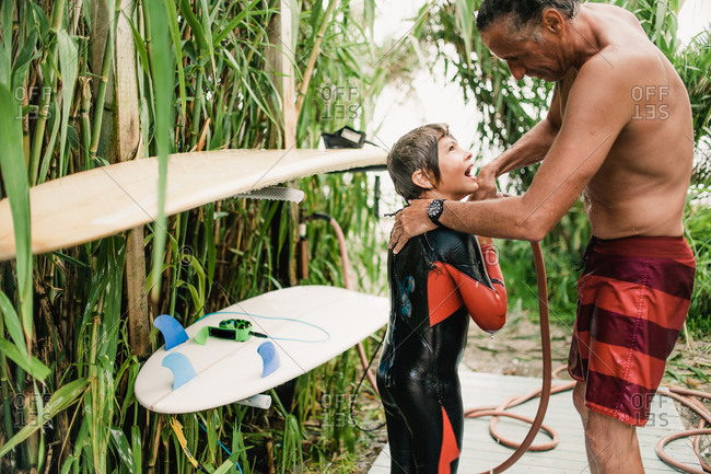 Dad helping his son rinse off after surfing