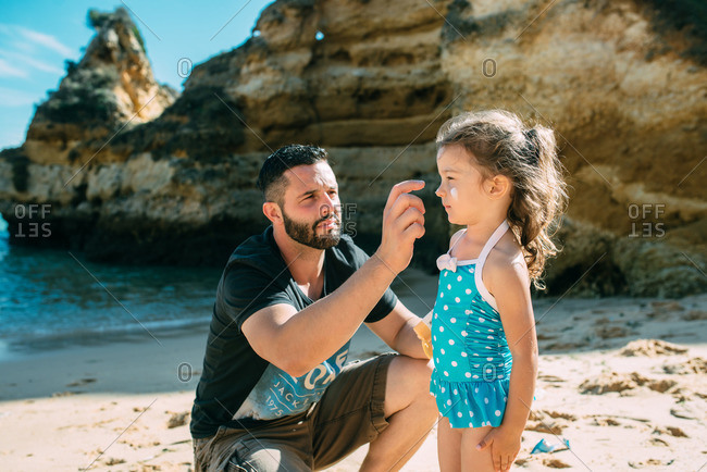 Dad putting sunscreen on girl at beach
