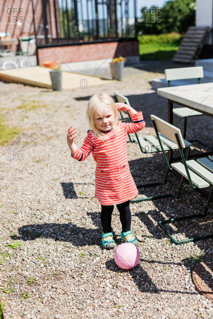 Young girl playing with ball in garden
