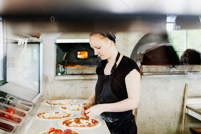 Chef making pizza in a restaurant with wood fired oven