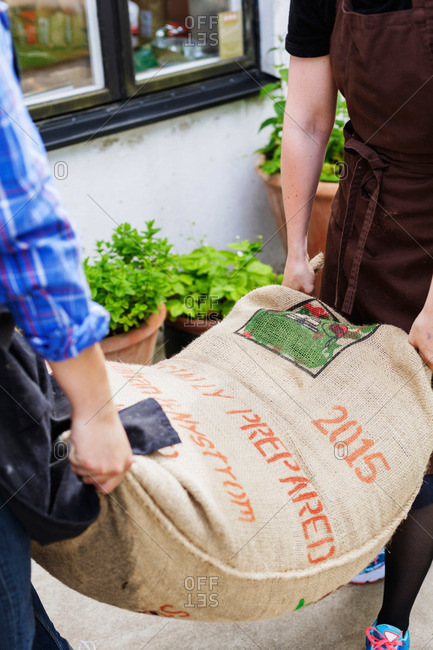 Two people carrying burlap bag of coffee beans