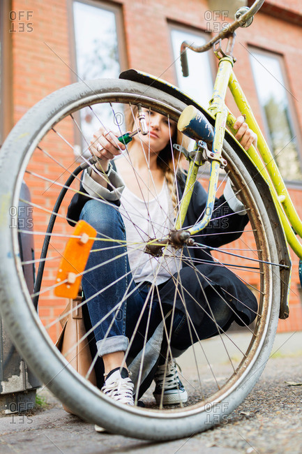 Woman connecting air hose to inflate bicycle tire